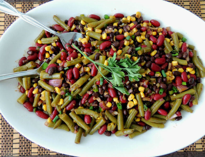 Southwestern Three Bean Salad Recipe -- A quick and easy side dish with a spicy dressing of lime juice, chili powder, garlic, and hot sauce. Just the right amount of kick! #vegan