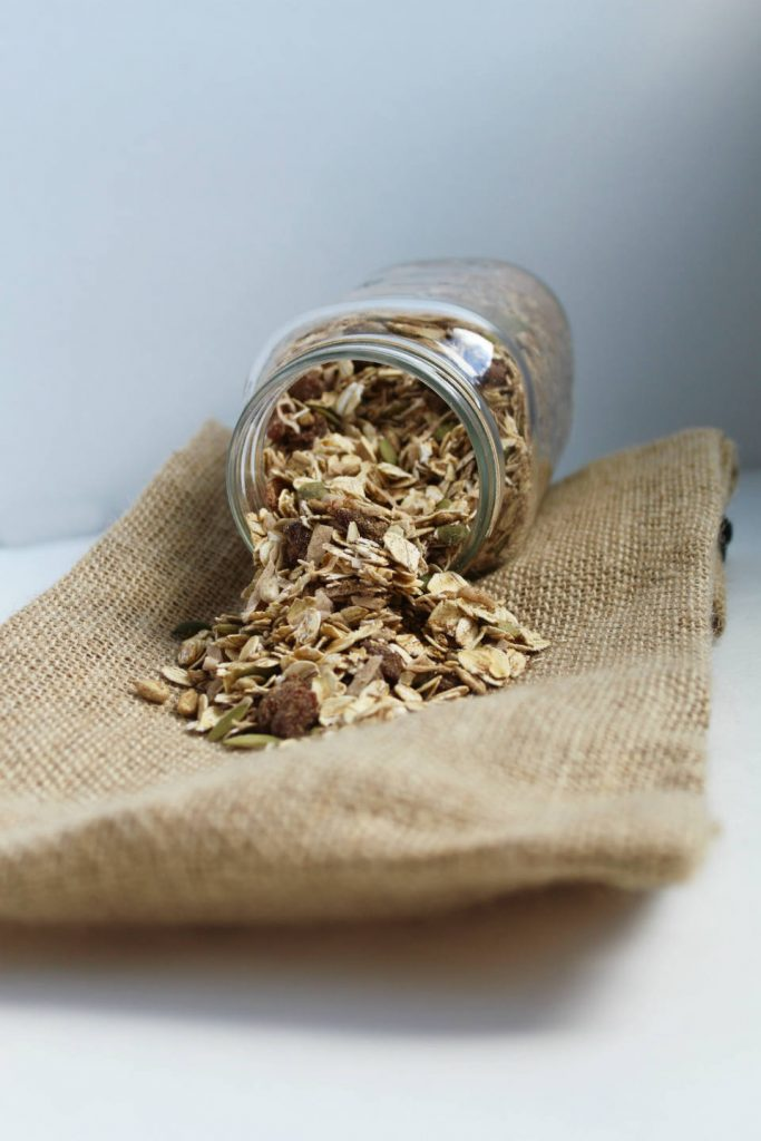 Pumpkin Spice Homemade Muesli Spilling Out of Jar on Burlap