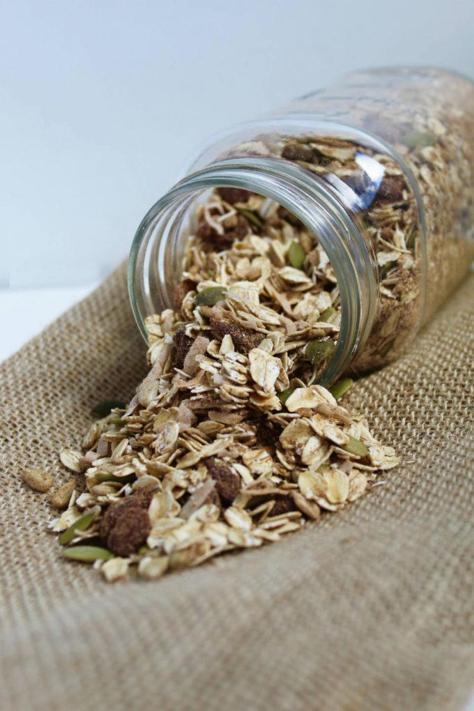 Pumpkin Spice Homemade Muesli Spilling Out of Jar onto Burlap