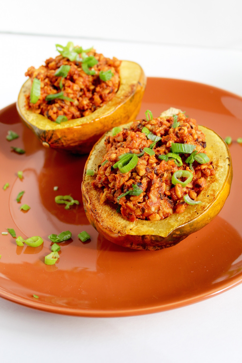 Smoky Tempeh Stuffed Acorn Squash Served On Orange Plate