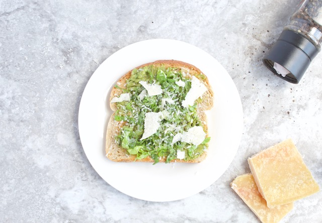 Caesar Salad Avocado Toast -- A simple avocado toast recipe mashed with garlic and herbs, and topped with dressed greens and freshly grated parmesan cheese. A veggie and fiber packed healthy snack! | @sinfulnutrition #sinfulnutrition #healthysnackideas #simpleavocadotoast