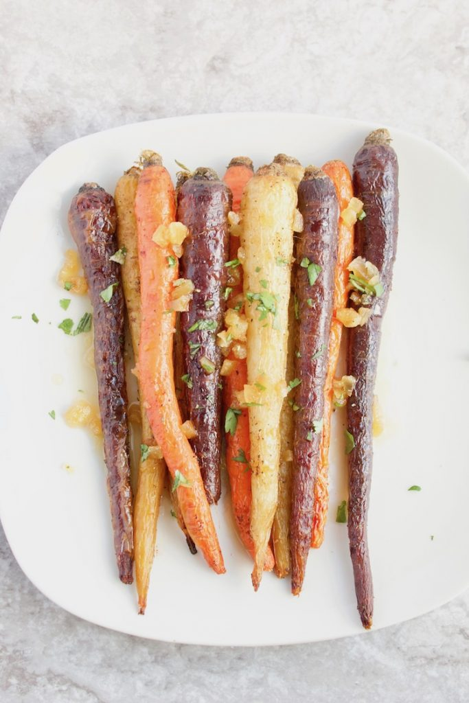 These extra gingery roasted rainbow carrots are soon to be your favorite veggie recipe! Drizzled with a sweet and spicy #maple ginger sauce makes these the perfect side to any #holiday #dinner! | #vegan | #glutenfree | @sinfulnutrition