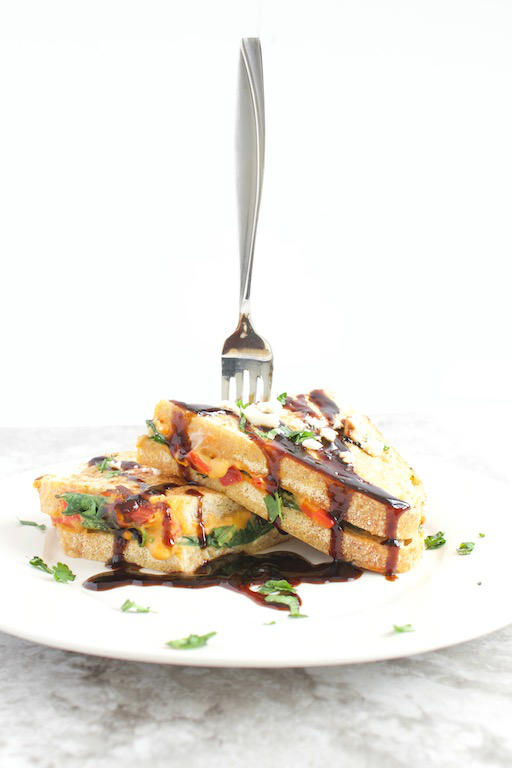 #AD Savory Stuffed French Toast -- A #vegetarian savory french toast #recipe made with sourdough bread, @sabra red pepper hummus, feta cheese, and sautéed spinach drizzled with a balsamic syrup. A meal fit for breakfast, brunch, or dinner! | @sinfulnutrition | #brunch | #breakfast | #thereciperedux | #sabra | #unofficialmeal | #frenchtoast