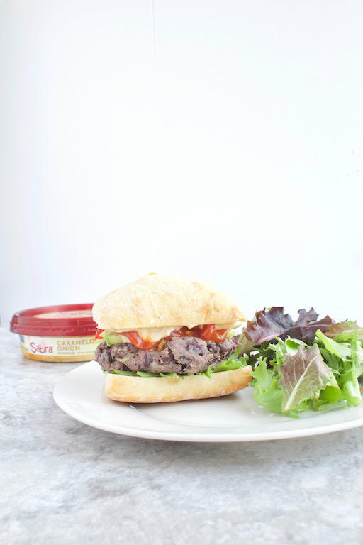 #AD Hummus Stuffed Burger Recipe -- A quick and easy bean #burger filled with caramelized onion @sabra #hummus. A healthy #plantbased dinner idea that only takes minutes and a few ingredients to make! | @sinfulnutrition | #vegan | #vegetarian | #glutenfree | #legumes | #dinner | #thereciperedux | #sabra