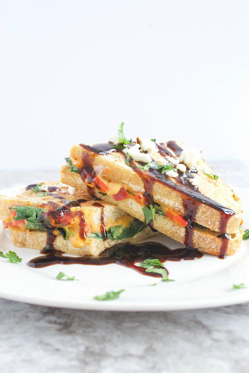 AD | Savory Stuffed French Toast -- A #vegetarian savory french toast #recipe made with sourdough bread, @sabra red pepper hummus, feta cheese, and sautéed spinach. A meal fit for breakfast, brunch, or dinner! | @sinfulnutrition #sinfulnutrition #thereciperedux | #sabra | #unofficialmeal | #savoryfrenchtoast