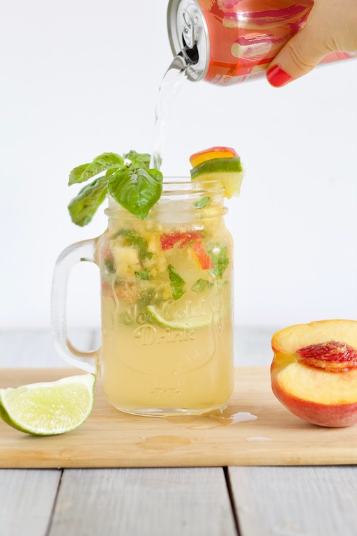 Basil Peach Mojito Recipe-- An end of the summer cocktail made with muddled peaches, fresh basil, and sparkling club soda. A refreshingly seasonal drink perfect for happy hour! | @sinfulnutrition | #sinfulnutrition | #cocktail | #drink | #happyhour | #rum | #summer | #summercocktail | #lowsugar