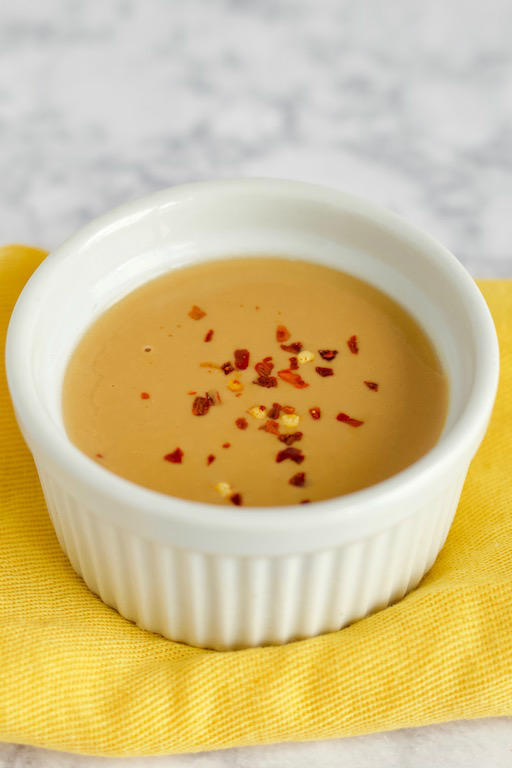 This easy peanut sauce recipe is made with only 5 simple ingredients you probably have on hand! The perfect healthy and gluten free condiment for peanut butter lovers! | @sinfulnutrition | #sinfulnutrition | #thaipeanut | #glutenfreepeanutsauce | #veganpeanutsauce | #peanutbuttersauce | #dippingsauce