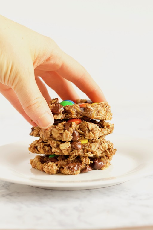 Hand grabbing stack of Healthy Monster Cookies