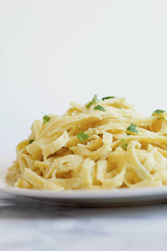 This Easy Dairy-Free Alfredo Sauce recipe is vegan, nut-free, & made with only 7 simple ingredients. You'll never guess the secret ingredient! | @sinfulnutrition #sinfulnutrition #veganpastasauce #veganalfredo #easyalfredosauce