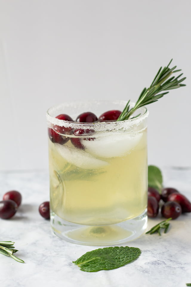 White Christmas Bourbon Smash in Short Glass with Rosemary Garnish