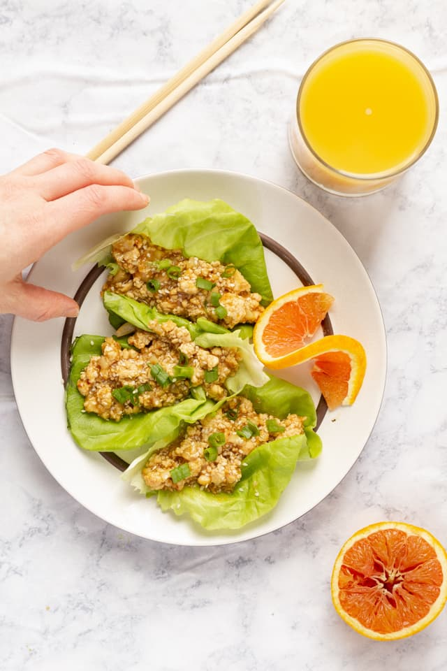 Hand Grabbing Orange Tofu Lettuce Wraps with Orange Juice