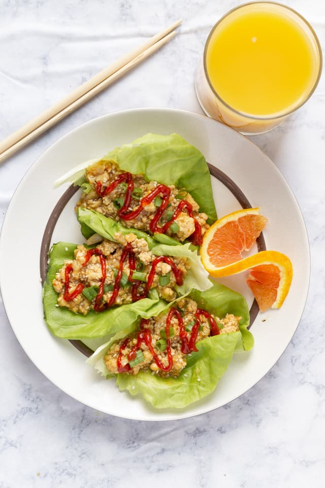 Orange Tofu Lettuce Wraps on Plate Overhead with Orange Juice