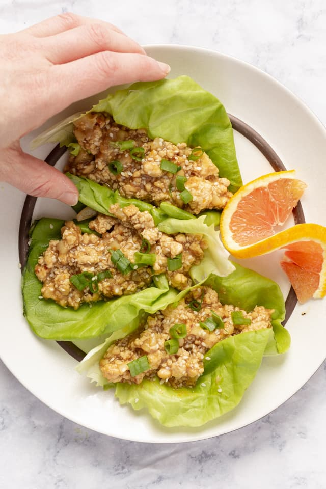 Orange Tofu Lettuce Wraps Hand Grabbing Close Up